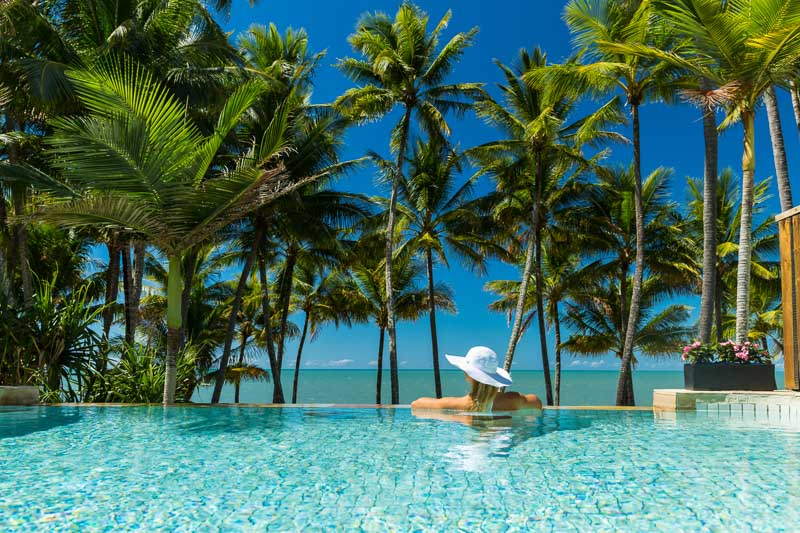 Woman relaxing in infinity pool overlooking tropical beach, Cairns