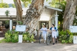 Young couple walking with bikes at The Reef House, Palm Cove