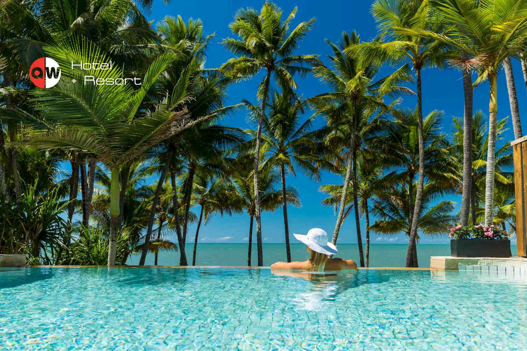 Woman swimming in resort pool overlooking palms trees and beach at Palm Cove by photographer Cairns