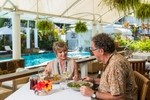 Mature couple dining by the pool at The Reef House, Palm Cove