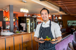 Portrait of chef holding a dish in Cairns restaurant interior