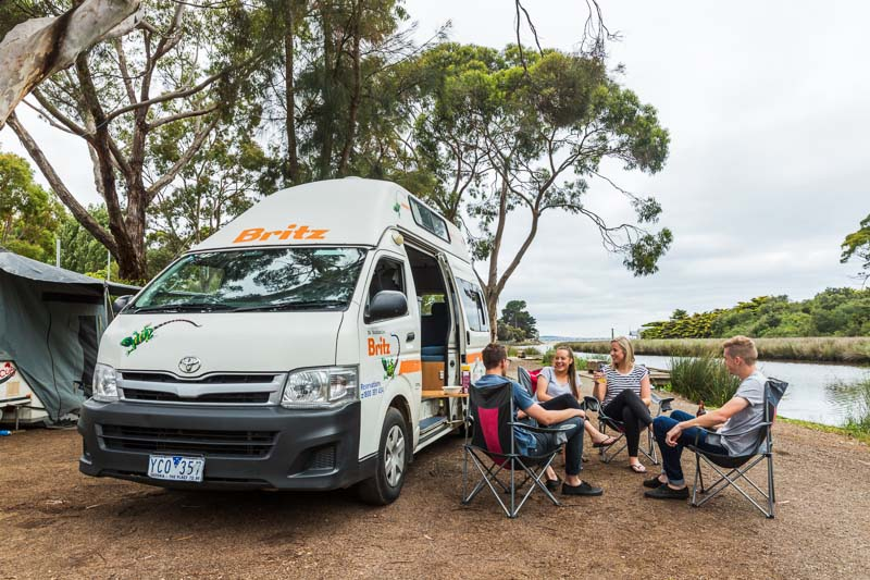 Group of young couples relaxing outside of campervan at riverside camping spot