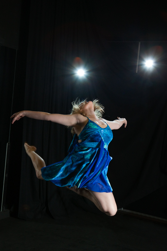 Female student performing contemporary dance with stage lights behind, Cairns