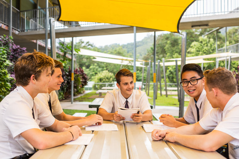A group of male high school students talking together at a table