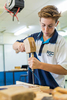 A high school student practising wood working skills with hammer and chisel