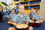 Portrait of happy students playing drums in school music class