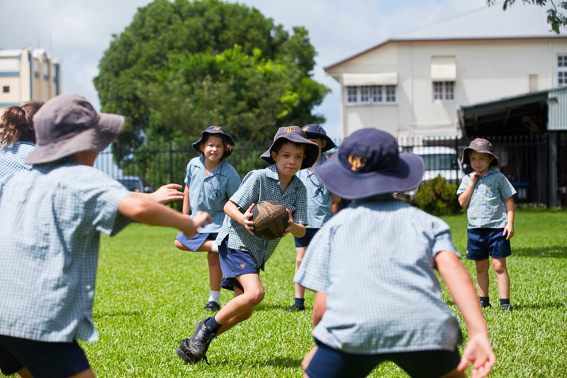 Active kids playing a game of touch football on school oval