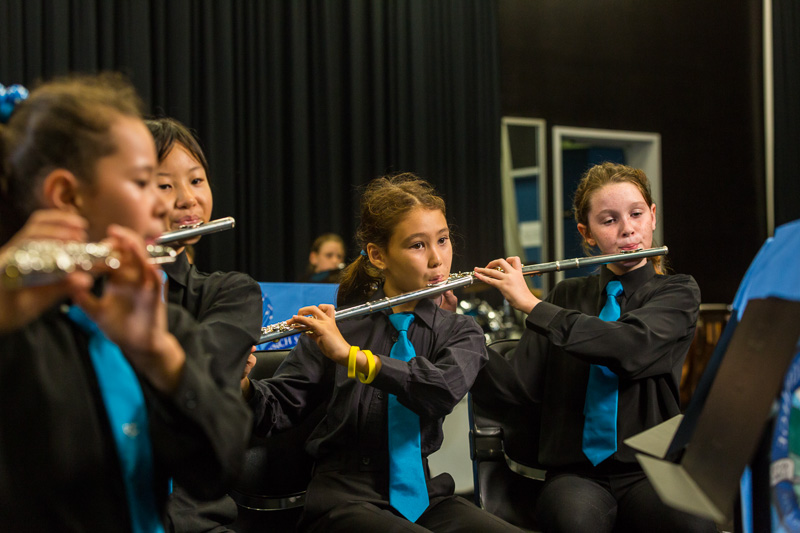 School students playing instruments in school orchestra performance