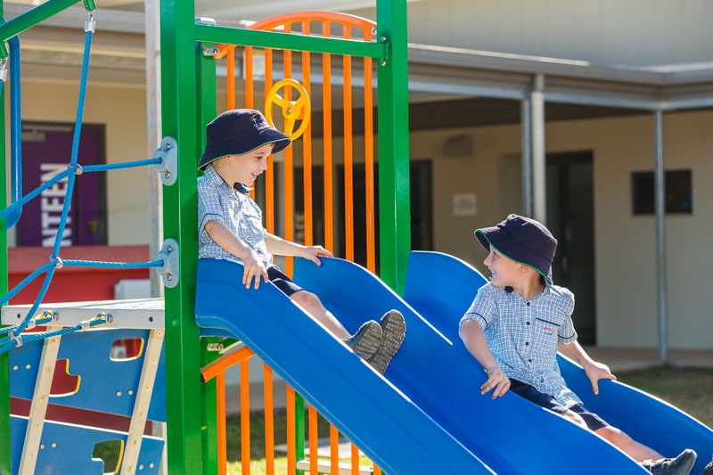 Two school boys having fun on slides in the playground