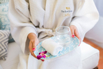 Woman holding refreshment towel at The Reef House spa, Cairns