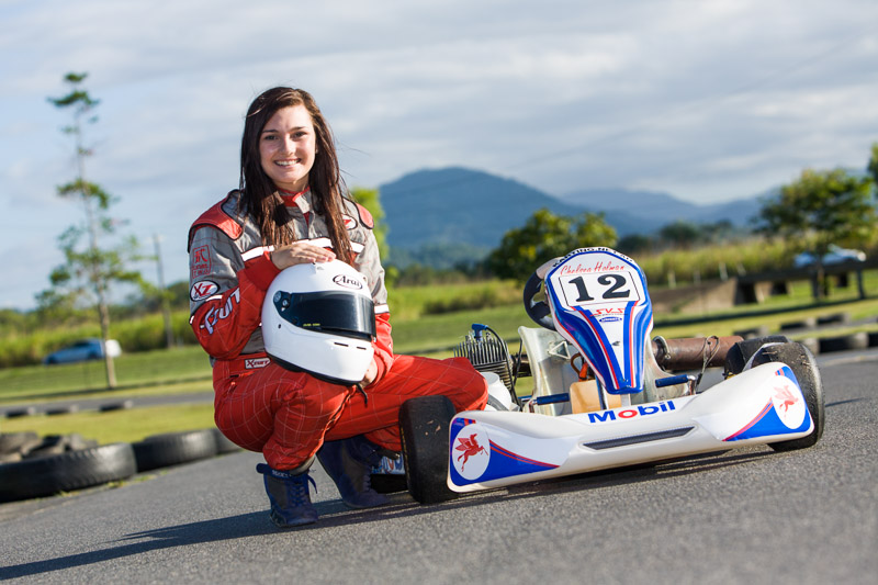 Portrait of young female gocart driver next to cart on racetrack, Cairns