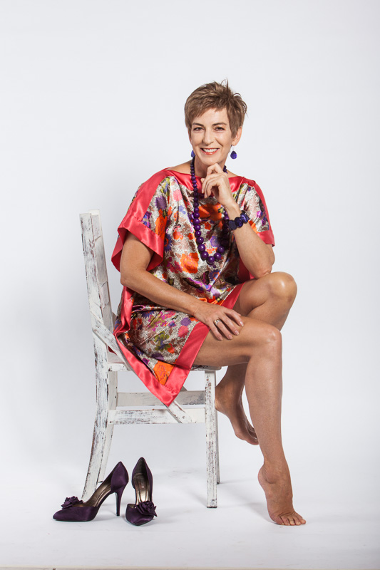 Portrait of woman sitting on chair in front of white studio background, Cairns