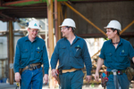 Three maintennace workers with hard hats and tool belts at a Sugar Mill, Cairns