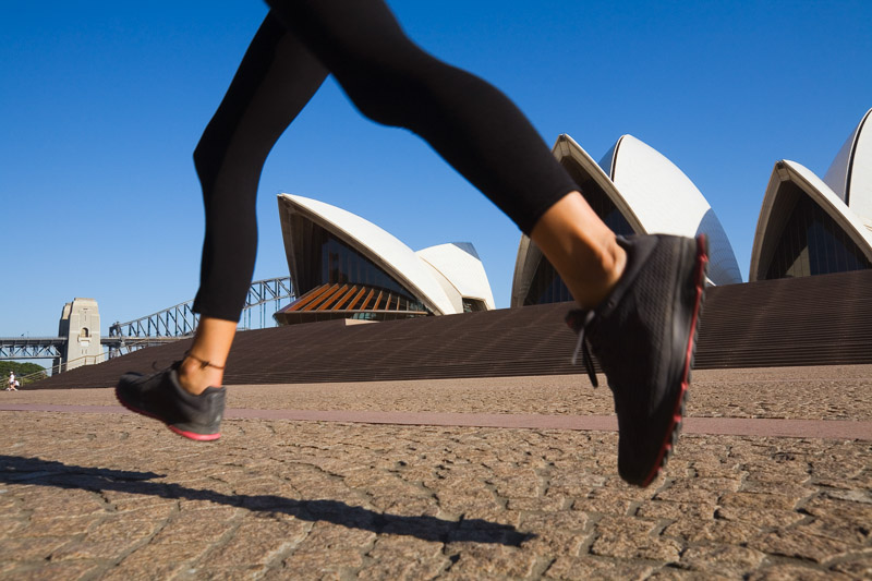 The Sydney Opera House framed by the legs of a morning jogger