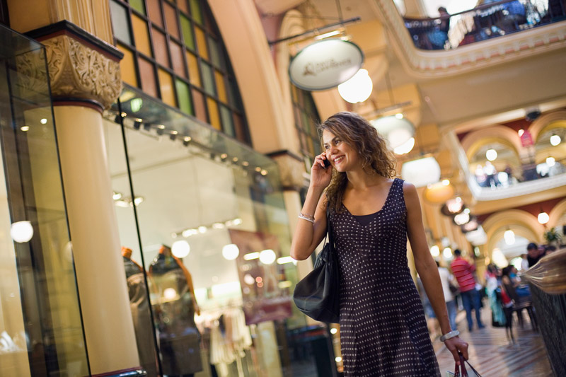 Young woman talking on phone and carrying shopping bags walking past boutique stores