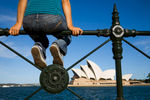 Woman sitting on harbour railing looking out to the Sydney Opera House