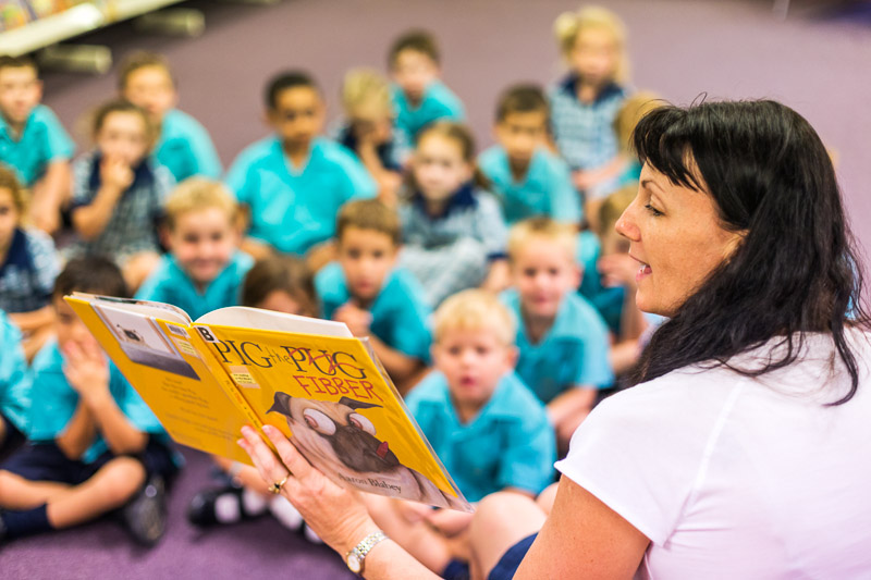 A school teacher reading a book to class of young students