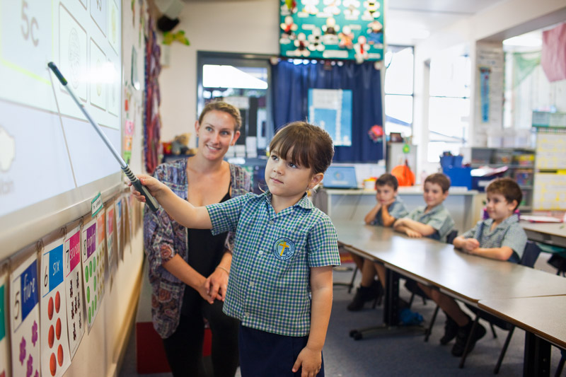 A teacher watches on as a young student points to the answer to a question on the whiteboard, Innisfail