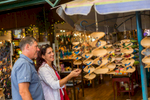 Mature couple looking at tourist handicrafts in a local market