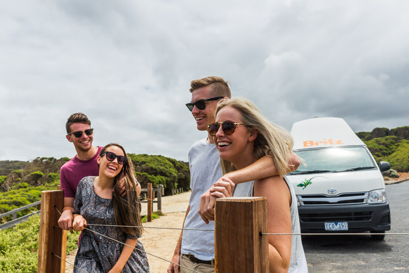 Two young couples laughing and smiling in front of roadtrip campervan