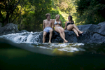 Young swimmers cooling off, sitting in a rainforest stream