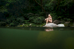 Woman sittting on a rock surrounded by the clear waters and rainforest surrounds of Mossman Gorge, Daintree National Park