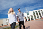 Young couple walking hand in hand outside Parliament House