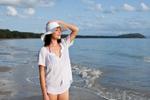 Young woman in beach wear looking along beach