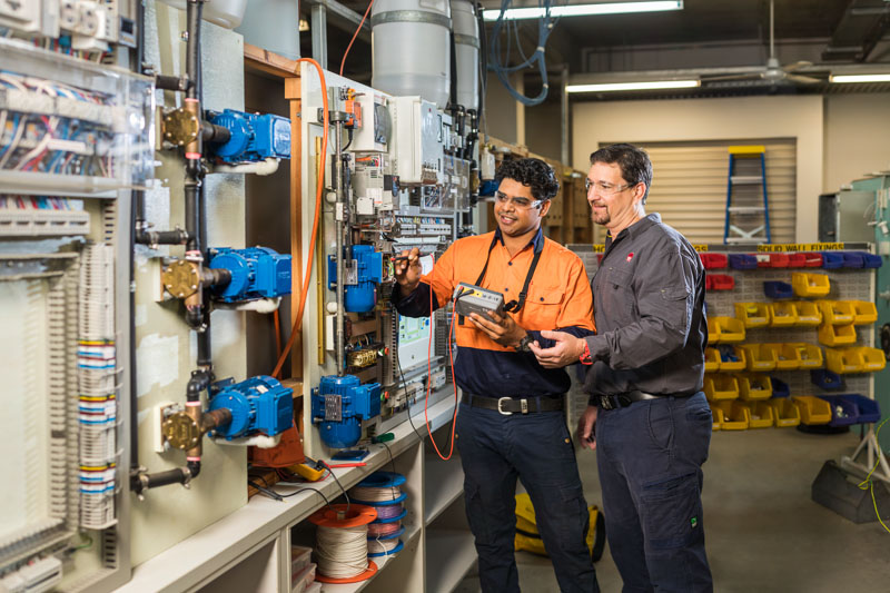 An electrotechnology supervisor instructing a student at a test wall, Cairns