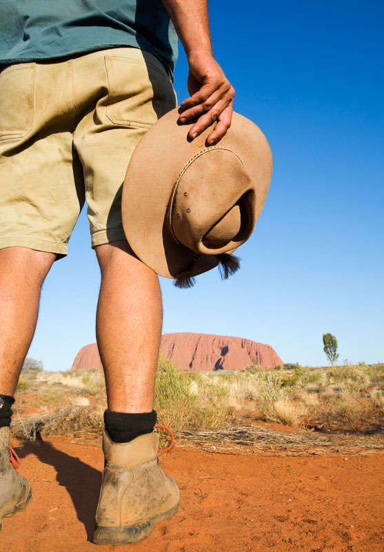 An outback guide holding an Akubra hat at side with Uluru beyond at Uluru-Kata Tjuta National Park