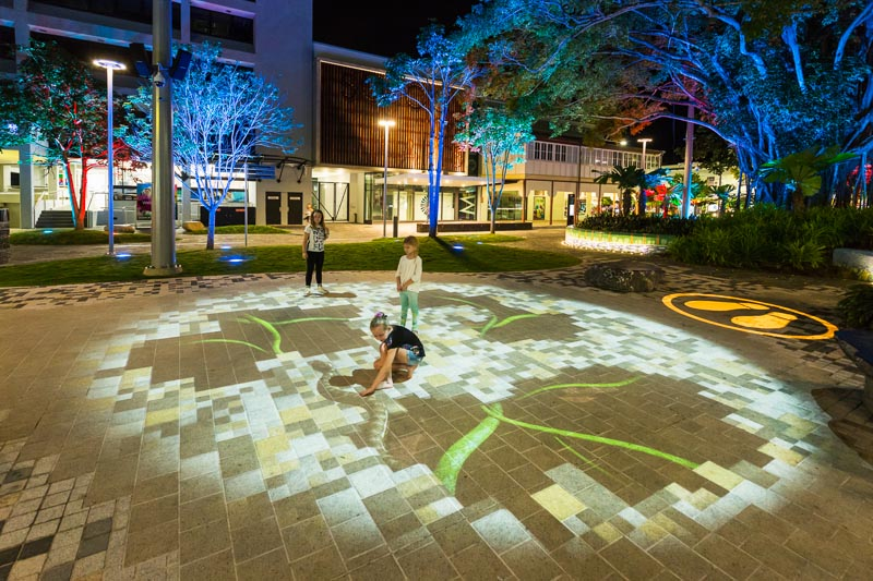 Children playing with light projections on the ground in Shields St, Cairns