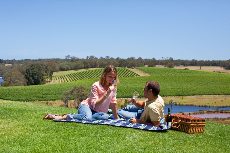 Young couple relaxing on a picnic rug with a wine overlooking the vineyard