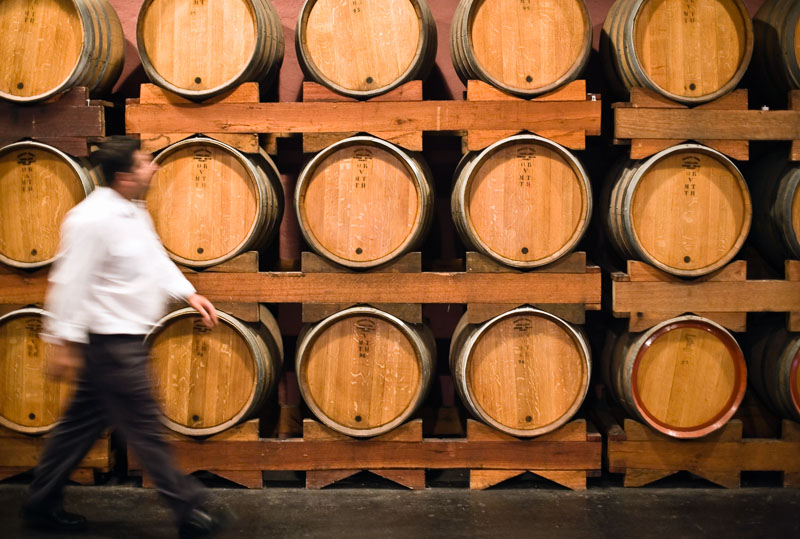 A man walks past rows of oak wine barrels at Hunter Valley winery
