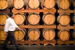 A man walks past rows of oak wine barrels at Hunter Valley winery