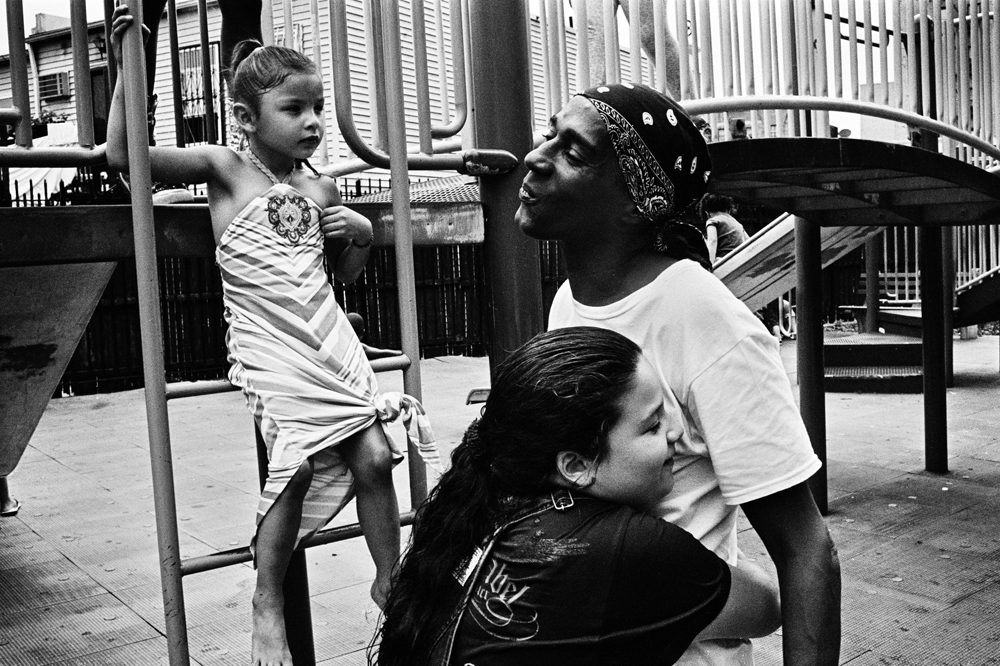 BRONX, NEW YORK - JUNE 22: Tamia Osorio, 10, hugs Wilfredo {quote}Sugar{quote} Gonzalez, while Kiara Asan, 6, plays in a park in the University Heights neighborhood of the Bronx, June 22, 2013.
