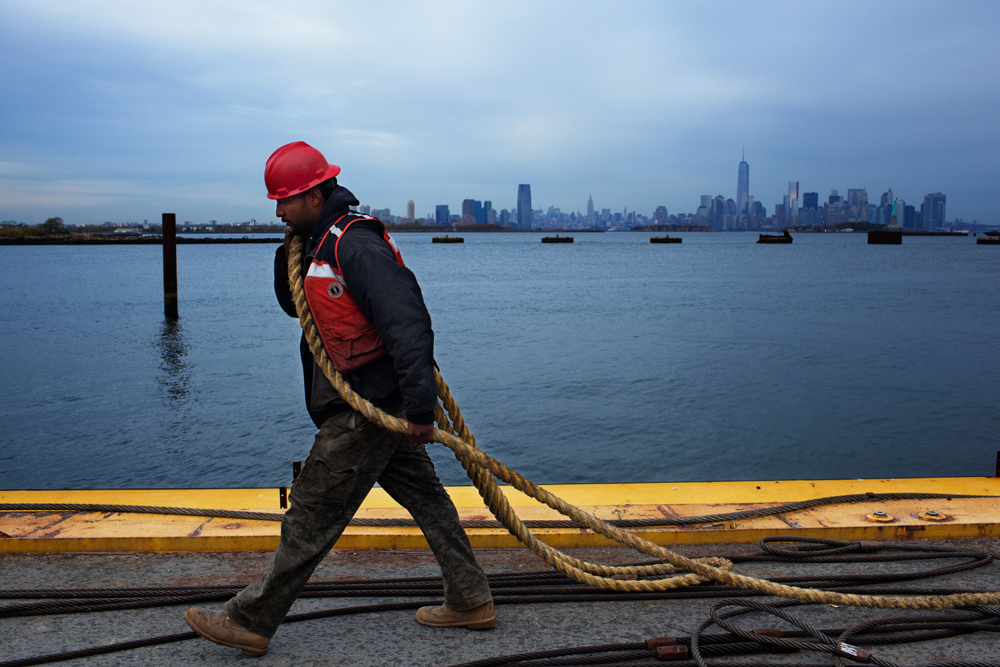 STATEN ISLAND, NY - OCT 22: Deckhand Walter Serrano carries a rope across a barge with the New York skyline in the background on October 22, 2013. Federal requirements have made it more difficult to acquire a mate's license, closing off the traditional {quote}hawse pipe{quote} route from deck to wheelhouse on a towing vessel.