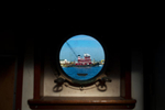 STATEN ISLAND, NY - OCT 22: A McAllister tugboat is seen through the porthole of the tugboat Freddie Miller on October 22, 2013. Founded in 1864, McAllister Towing & Transportation is one of the oldest and largest family-owned marine towing and transportation companies in the United States.