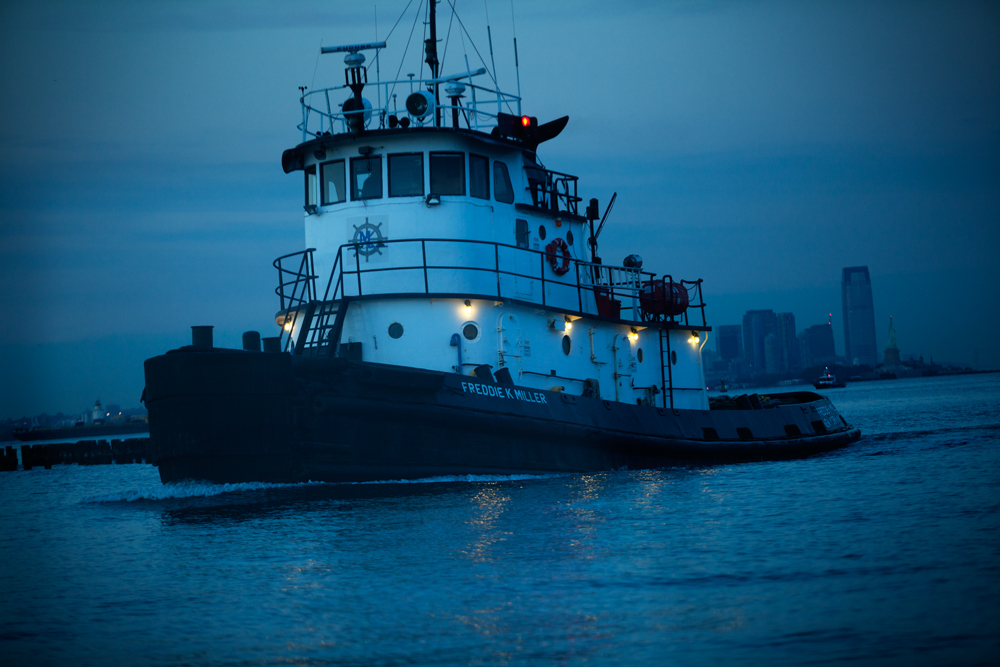 NEW YORK, NY - OCT 27: The tugboat Freddie Miller approaches Miller's Launch on the North Shore of Staten Island on October 27, 2013. Miller's Launch has a fleet of 32 vessels including tugboats, supply boats, crew boats and barges, all traditionally named after family members.