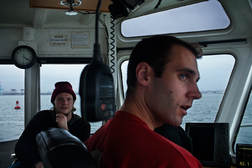 STATEN ISLAND, NY - MAR 19: Deckhand Jesse Rivera, left, and First Mate Kyle Setta in the wheelhouse of the tugboat Ellen McAllister as they help sail a container ship through the Kill Van Kull on March 19, 2014. Setta graduated from the U.S. Merchant Marine Academy, as opposed to taking the traditional {quote}hawse pipe{quote} route from deck to wheelhouse on a towing vessel.