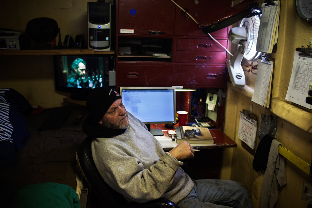 STATEN ISLAND, NY - MAR 19: Engineer Dean Kinnier smokes a cigarette in his quarters on the tugboat Ellen McAllister on March 19, 2014. Kinnear and the boat's five to six member crew spend 14 days on the tugboat, 14 days off, working in six-hour shifts.