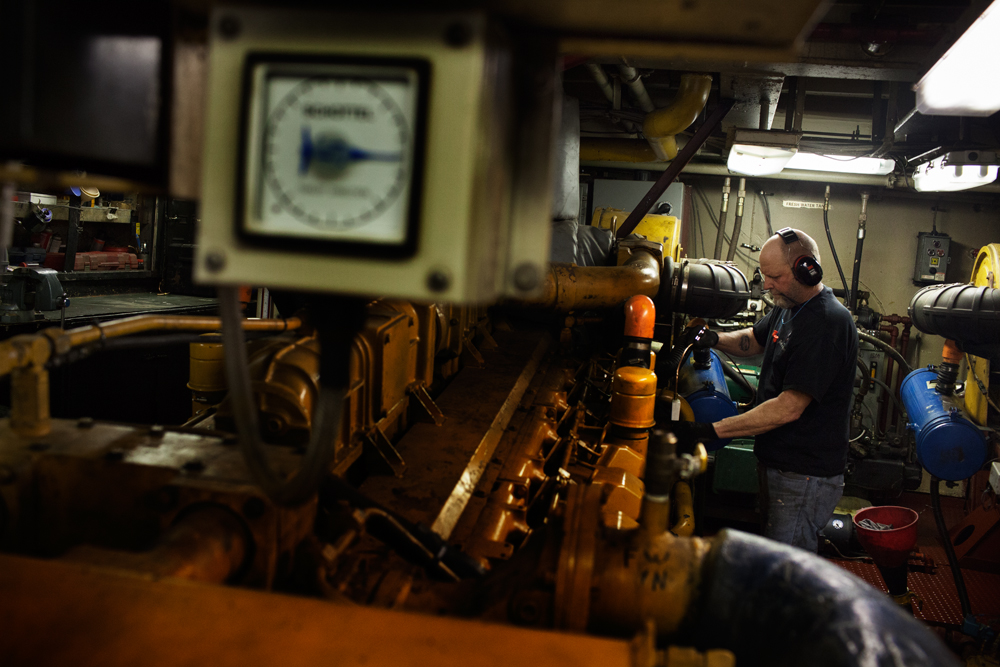 STATEN ISLAND, NY - MAR 19: Engineer Dean Kinnier conducts maintenance on one of the two diesel engines aboard the tugboat Ellen McAllister on March 19, 2014. McAllister Towing & Transportation's fleet consists of more than 70 tugboats, including 20 working out of New York Harbor.