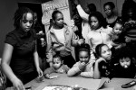 SOUTH BRONX, NEW YORK - MAR 7: Eshey Scarborough's birth daughter Marshey, left,  prepares to cut the cake at a birthday party for foster child Envy Scott March 7, 2009. Eshey and her partner Paris Harris run a foster home for at-risk youth in the the South Bronx.