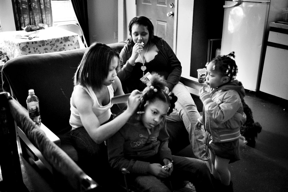 SOUTH BRONX, NEW YORK - MAR 28: Foster child Shalena Scott, 18 years old, braids the hair of Naya, Eshey Scarborough's grandaughter March 28, 2009.
