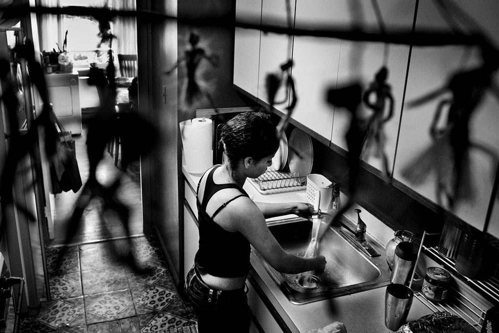 SOUTH BRONX, NEW YORK - APR 26:  Surrounded by the figures of a Yoruba mobile, 16-year-old foster child Daybelis Ramirez washes her dishes after breakfast April 26, 2009.