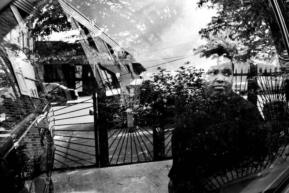 SOUTH BRONX, NEW YORK - MAY 2: Foster parent Paris Harris unloads groceries from her SUV, with the South Bronx neighborhood reflected in the window May 2, 2009.
