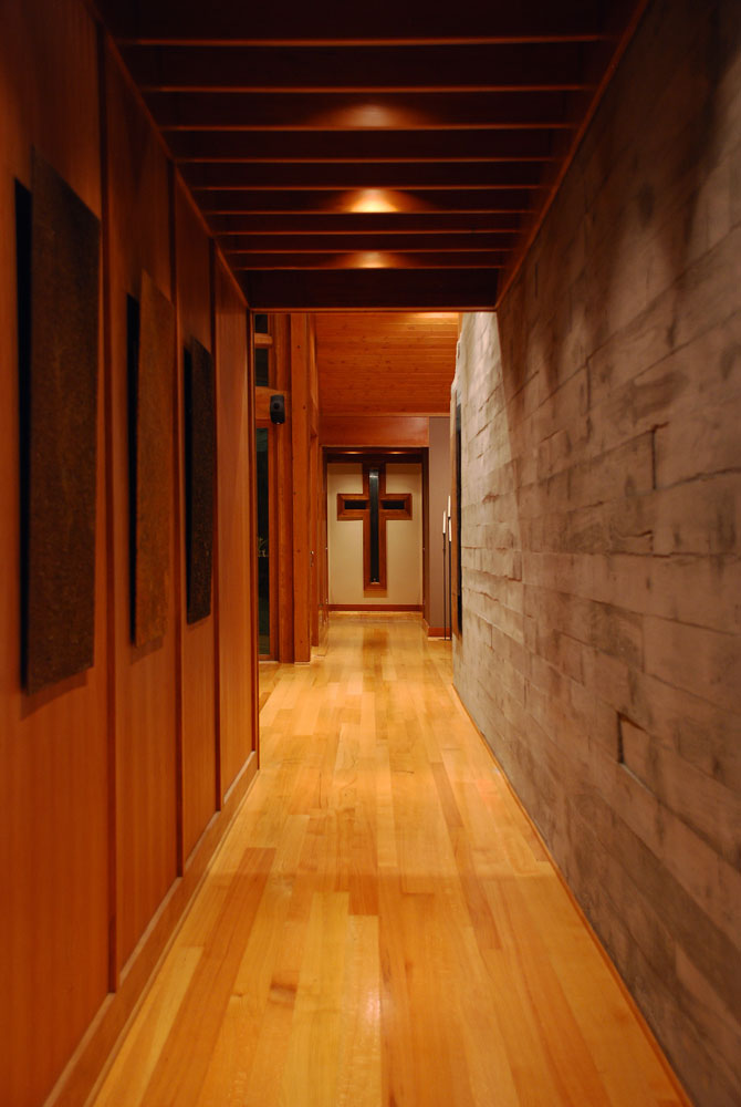 Interior entry hall showcasing exposed concrete and cherry wood paneling in a custom designed home by Pavelchak Architecture in Valle Crucis, North Carolina, near Boone
