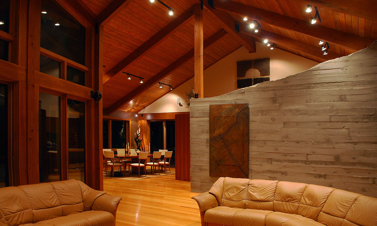 Living room / greatroom showcasing exposed concrete and cherry wood paneling in a custom designed home by Pavelchak Architecture in Valle Crucis, North Carolina, near Boone