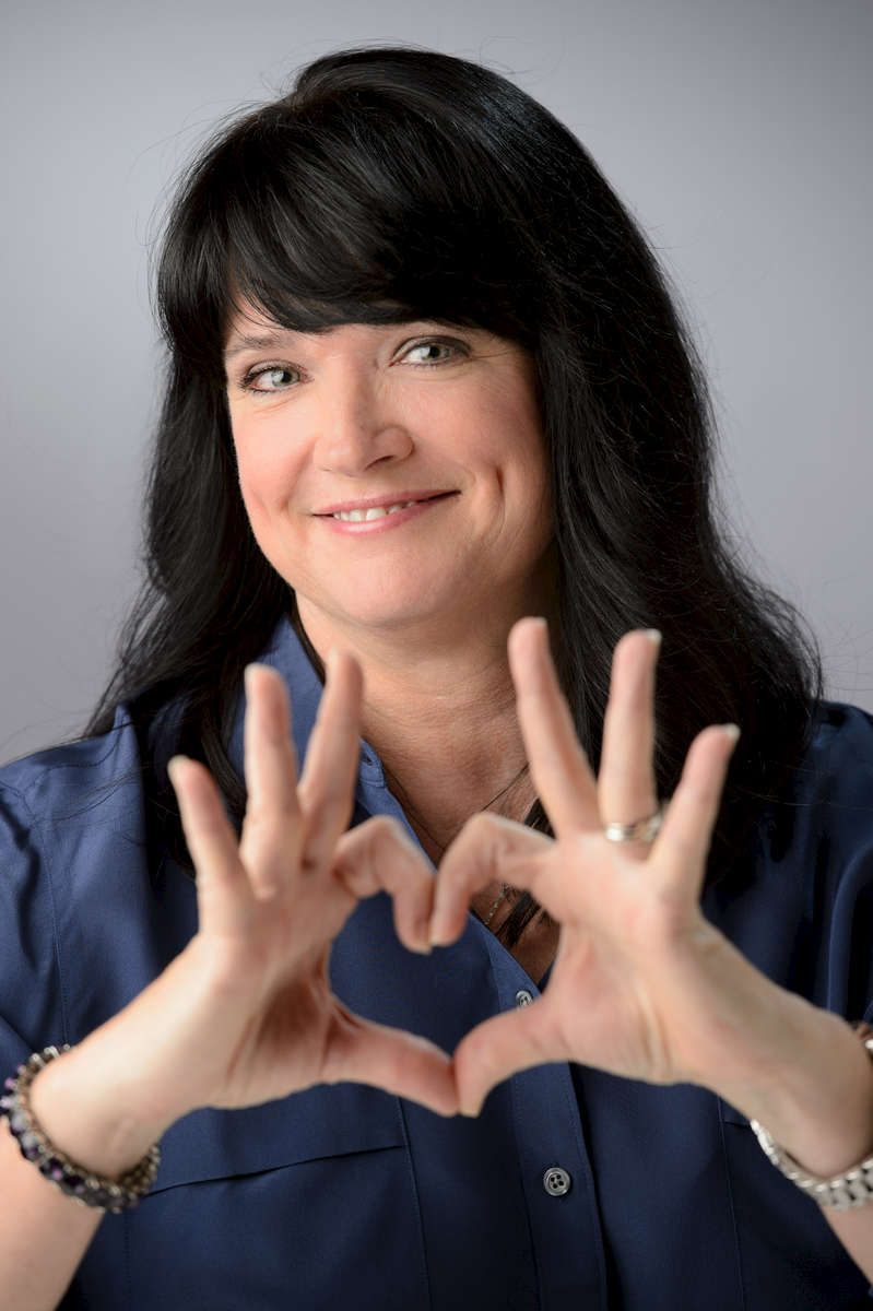 Portrait of Sue Clifton holding her fingers in a heart shape