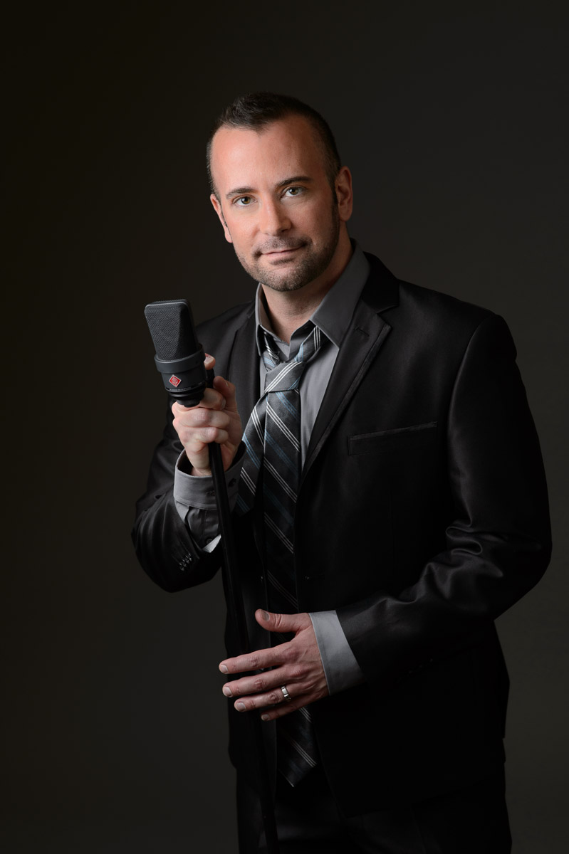 Portrait of a singer in a black sut with a microphone