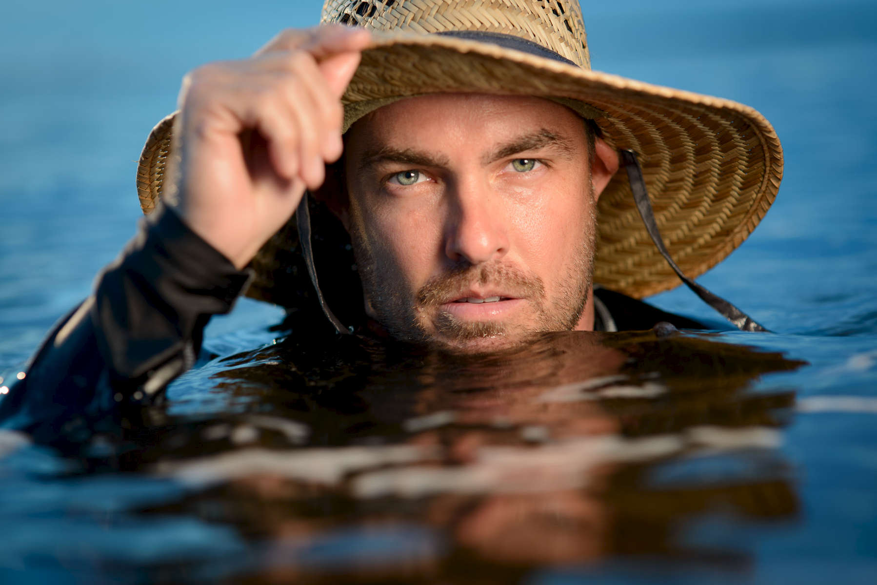 Man in a hat up to his chin in the water.